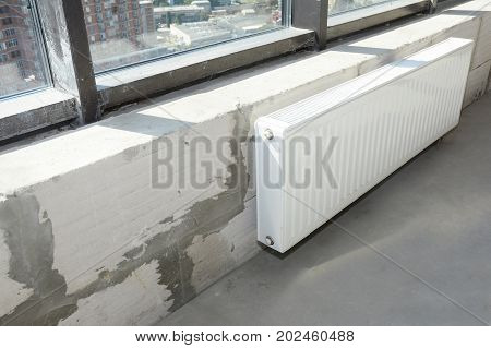 Installing metal white radiator heating with thermostat in new house construction.