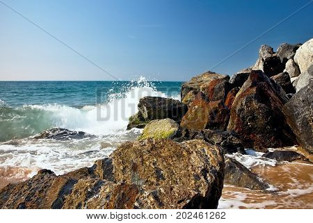 Sea waves and rocks on the beach in Malgrat de Mar, Spain. Salty sea water, waves, sun, sand, rocks and holidays summer and heat