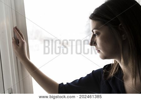 A 30 year old woman stands in front of the window
