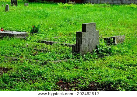 Forgotten cemetery in the city, destroyed gravestones and monuments.
