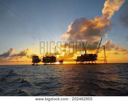 Offshore oil and gas platform in the middle of the ocean with beautiful sunset.