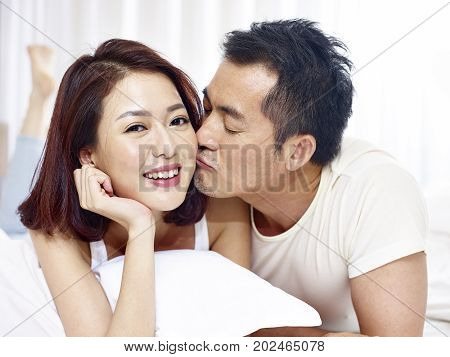 loving asian couple lying on front and kissing in bed.