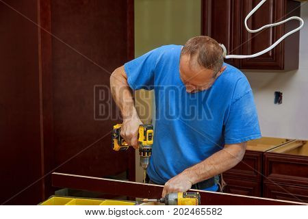 technician man installing kitchen cabinets Installation of kitchen cabinet.