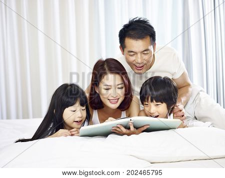 happy asian family with two children lying on front in bed reading a book together.