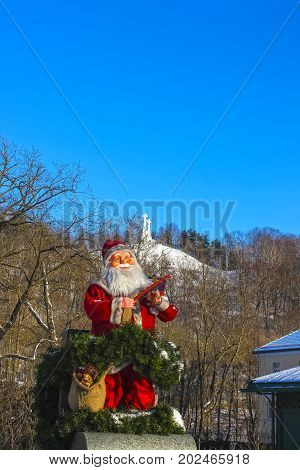 The Christmas Santa Claus against Monument of Three Crosses on the Bleak Hill at the dawn time in Vilnius, Lithuania.