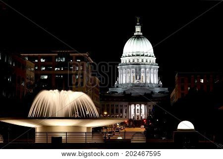 National Historic Landmark. Madison Wisconsin USA. Night scene with official buildings and illuminated fountain on the foreground. View from Monona terrace balcony horizontal composition.