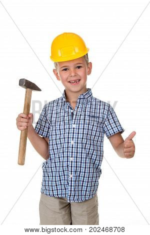 Cute boy in blue checkered shirt and yellow building helmet, holding a hammer in one hand and showing thumbs up, on white isolated background