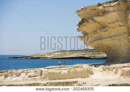 Malta wild cliffs and deserted coast, playing children next to the sea