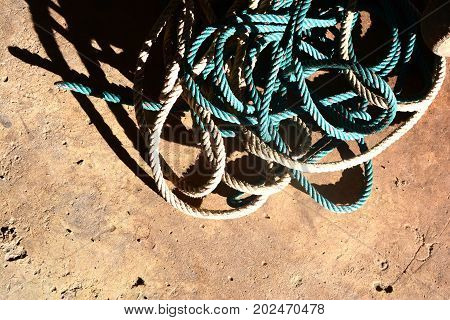 The tangled rope on cement ground with hard light and shadows