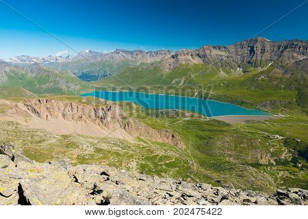 High Altitude Blue Lake, Dam On The Italian French Alps. Expansive View From Above, Clear Blue Sky.