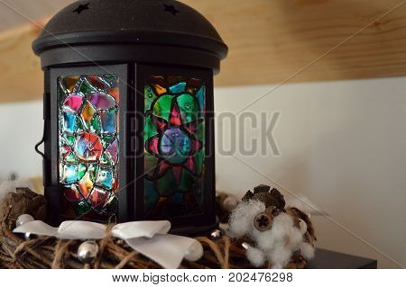 stained-glass metal lantern on a wooden background close-up