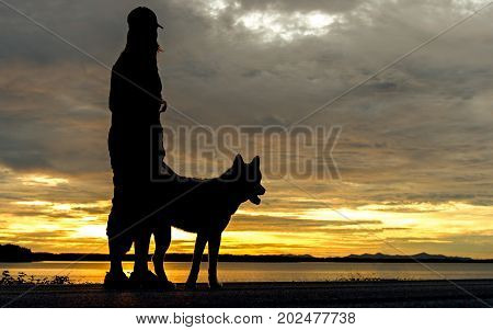 Silhoutte relaxed woman and dog enjoying summer sunset or sunrise over the river stand at near lake. Lifestyle Concept