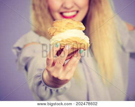 Sweet food and happiness concept. Funny joyful blonde woman holding yummy choux puff cake with whipped cream excited crazy face expression. On violet