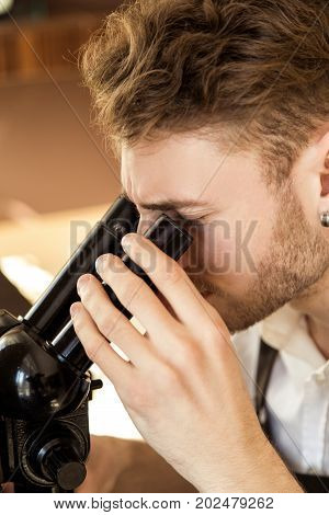 Jeweler Examines The Ring Through A Microscope