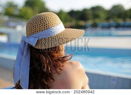 Young woman with long brown hair and a straw hat and she relaxes in the exclusive luxurious tourist resort on the edge of the pool