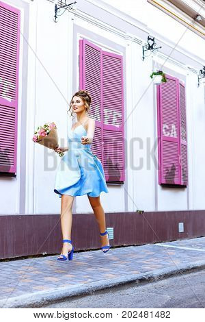 Young Woman Running With A Bouquet Of Flowers On A Summer Day Outdoors