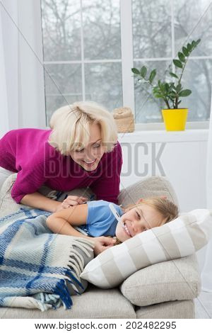 Sick liitle girl lying on sofa at home. Mom and daughter smiling, mom taking care of her sick child.