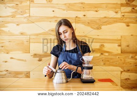Barista Brewing Coffee In The Cafe