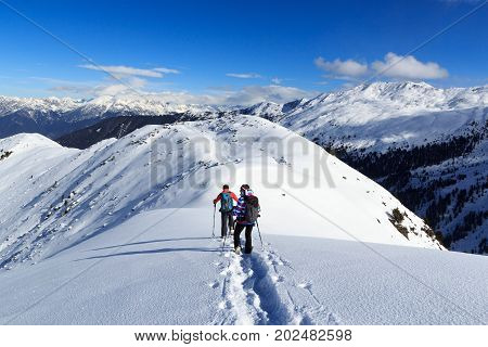 Sellrain, Austria - February 10, 2017: Man and woman hiking on snowshoes and mountain snow panorama with blue sky in Stubai Alps. Snowshoeing is a very popular sport in the Alps during winter.