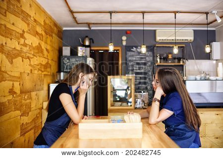 Two Cute Girl Barista Sitting At A Wooden Table In A Coffee House