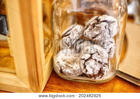 Scented glazed gingerbread in a transparent glass jar are on the table in a cafe. Close-up view