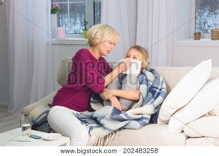 Mother taking care of her sick child, wiping her face with handkerchief. Caring mom staying with ill daughter.