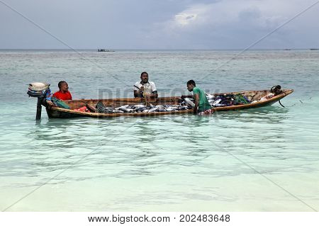 Stone Town (Zanzibar) Tanzania - January 7 2016: A dhow (traditional sailboat) in the background and a crowded fishing boat and fishman in the foreground in the Indian Ocean just off the island of Zanzibar Nungwi