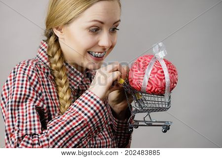 Happy woman holding shopping cart with brain inside. Clever responsible buying concept.