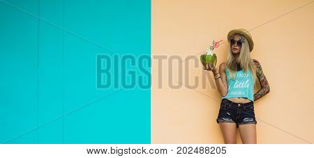 Beautiful young blonde hipster in denim shorts and a straw hat, sunglasses stands amid the brightly colored walls with a coconut in hand. Tropical weekend, beach party. Thai