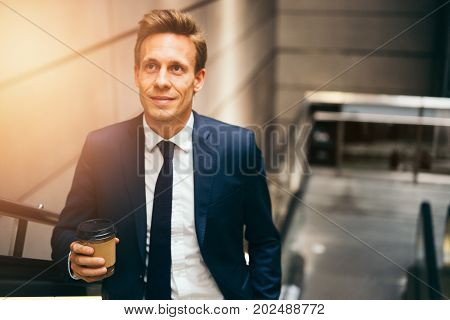 Executive Drinking Coffee And Riding An Escalator During His Com