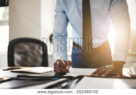 Young Businessman Leaning On His Office Desk Signing Documents