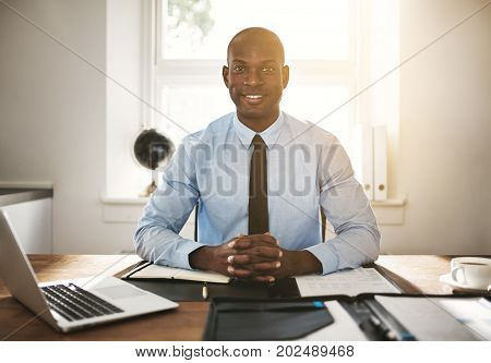 Smiling Young Executive Sitting At His Work Desk