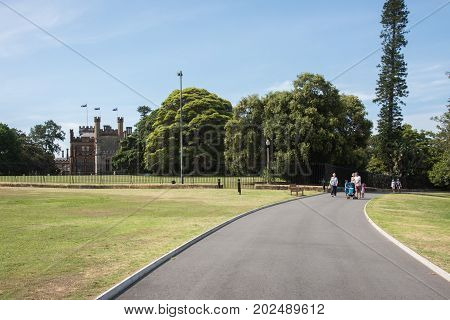 SYDNEY,NSW,AUSTRALIA-NOVEMBER 20,2016:  Governor's House and tourists on path at the Royal Botanic Gardens in Sydney, Australia