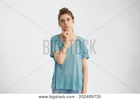 Pciture Of Emotional Young Female Having Frustrated Doubtful Expression, Holding Hand On Her Face, T
