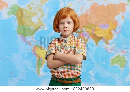 Seious Small Male Boy With Ginger Bobbed Hair, Keeping Hands Crossed While Standing Against Map, Com