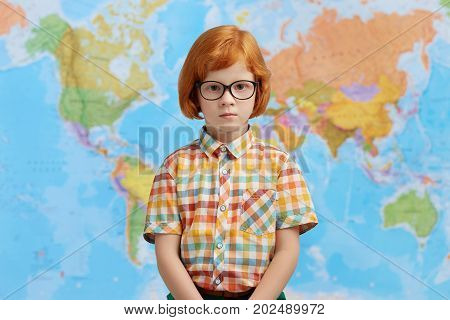Little Boy With Ginger Hair, Wearing Checkered Shirt And Eyeglasses, Standing Against Map Background