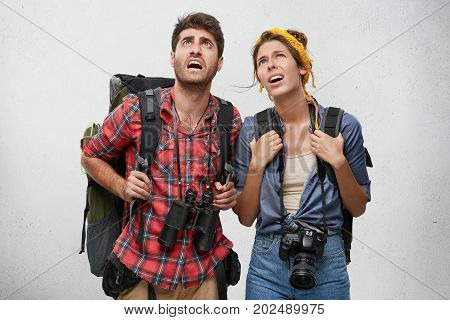 Picture Of Worried Male And Female Tourists, Looking At Schedule Of Trains, Being Tired After Spendi