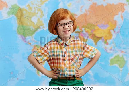 Photo Of Smiling Boy With Ginger Hair, Wearing Glasses, Keeping Hands On Waist, Having Joy While Sta