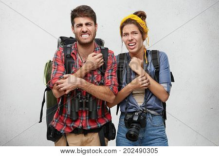 Studio Portrait Of Unhappy Male And Female Tourists With Backpack, Camera And Binoculars, Scratching