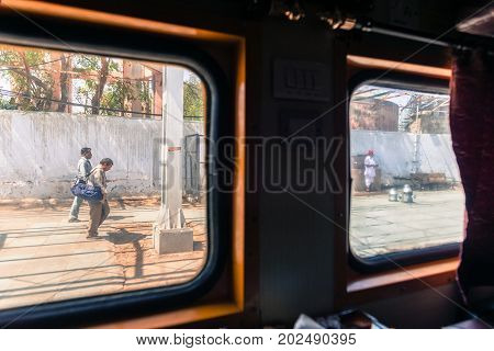 JAIPUR RAJASTHAN INDIA - MARCH 10 2016: Horizontal picture from inside India's train of indian people walking in the platform in Jaipur.