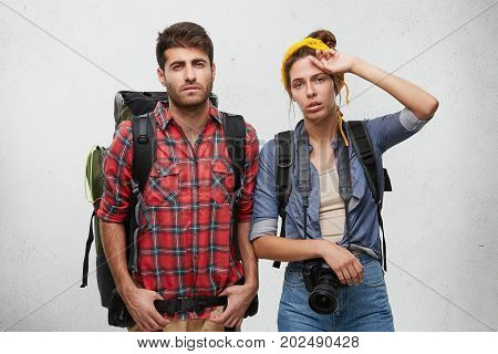 Picture Of Exhausted Frustrated Guy And Girl Of European Appearance Carrying Rucksacks On Their Shou