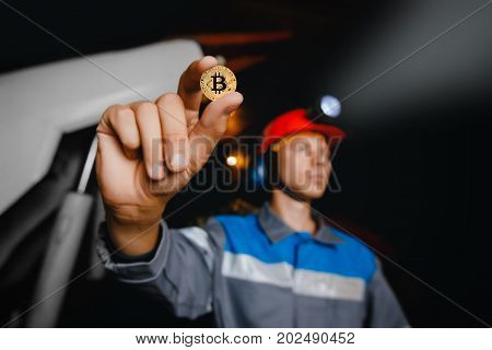 A man holds a coin in his hand Bitcoin mining