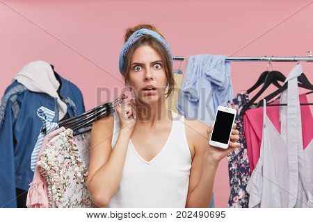Angry Young Pretty Woman Looking With Dissatisfaction Into Camera, Keeping Hangers With Clothes On S