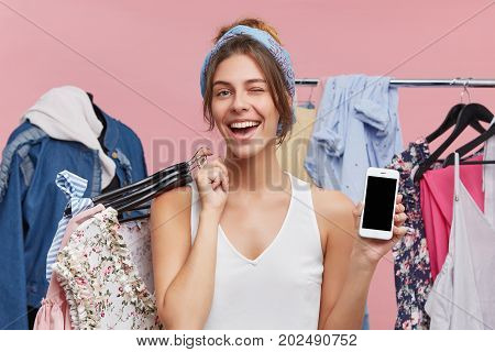 Happy Young Woman Showing Blank Copyspace Display Of Mobile Phone, Holding Hangers Of Stylish Pieces