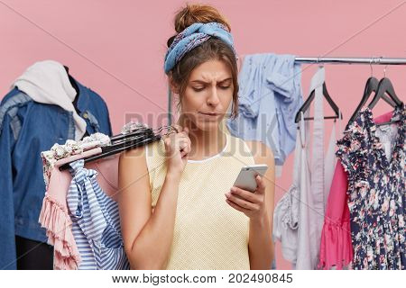 Serious Female Model Standing Agianst Lay Figure And Rack Of Clothes, Holding Hangers With Clothes I