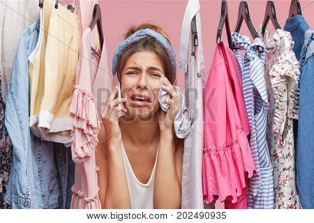Frustrated Woman Standing Near Rack Full Of Clothes, Chatting With Her Friend Over Smart Phone, Comp