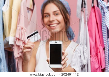Glad Positive Female Standing Near Rack With Clothes, Showing Mobile Phone And Credit Card While Doi