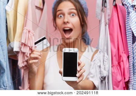 Astonished Female Model Looking With Bugged Eyes And Widely Opened Mouth Into Camera While Holding C