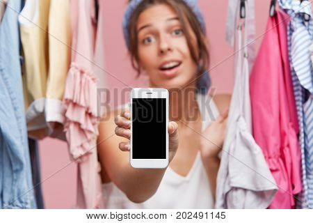 Cropped Shot Of Beautiful Female Holding Mobile Phone With Blank Screen While Standing Near Rack Wit