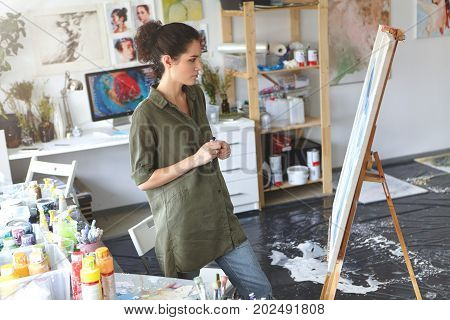 Beautiful Young Brunette Female Painter Dressed Casually Standing In Front Of Her Painting, Studying